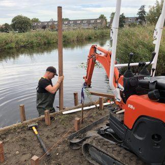 Hardhouten palen in de grond drukken met Kubota u10-3 voor een vlonder | Direct bestrating